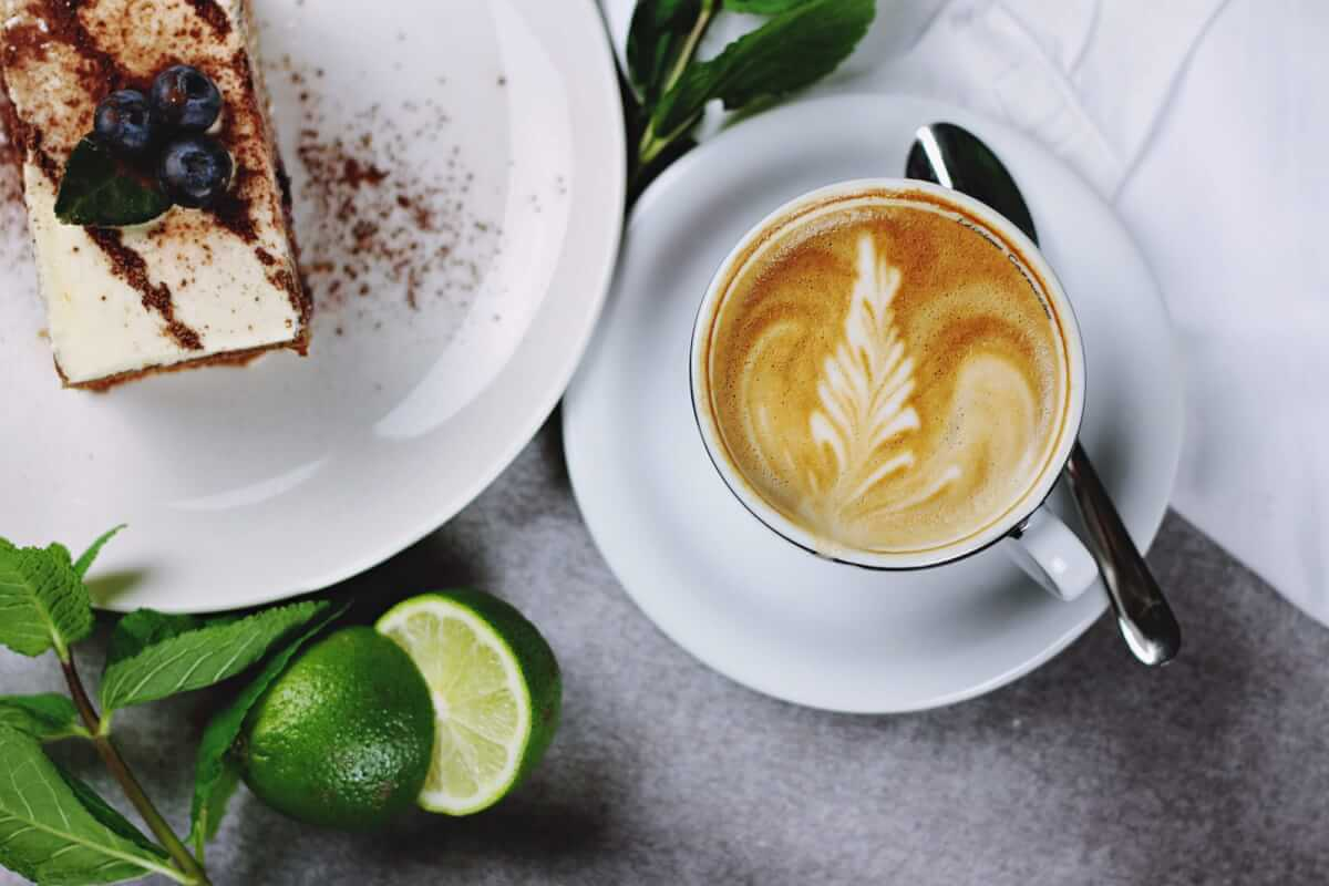 A coffee next to cake and a lime