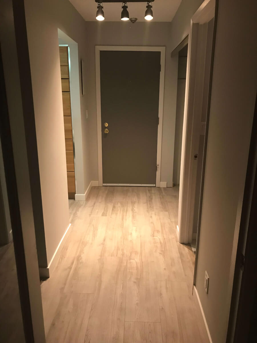 Photo of finished hallway with new wide-plank light grey laminate flooring, dark grey door, light grey trims, and lighter grey walls.