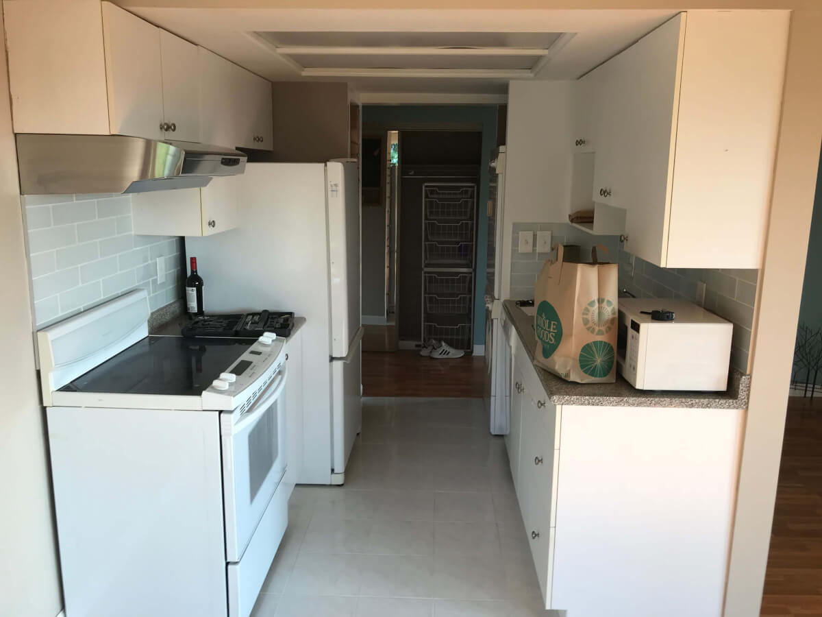 A photo looking through my galley kitchen. White appliances with white, large square tiling.