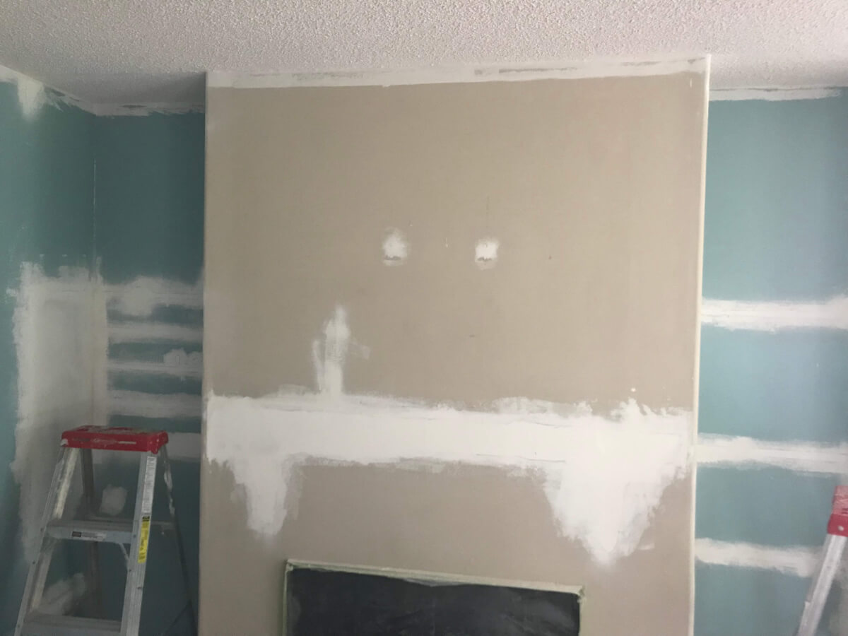 Photo of the area above the fireplace just after the first patching after removing the fireplace and knocking down the shelves. The ceiling has also had the first coat of off-white paint.
