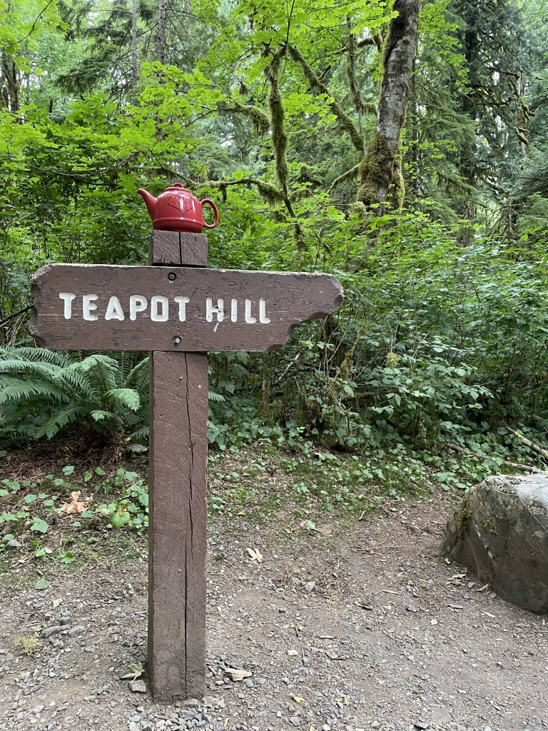 """A photo of a hand-made signpost that reads """"Teapot Hill"""" pointing to the right. On top of the sign is a large red teampot."""
