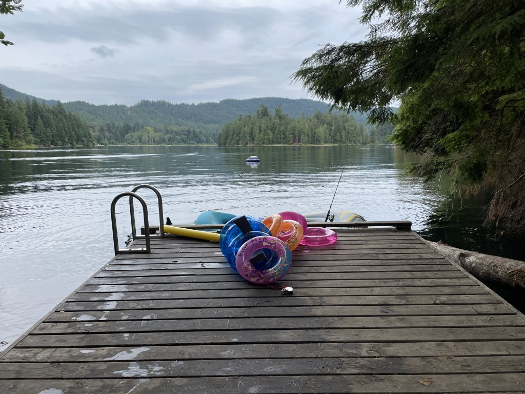 A picture of Weaver Lake with the small dock in the foreground. On the dock are some of our floaties, and a small inflatable boat with a fishing rod. No fish were caught.