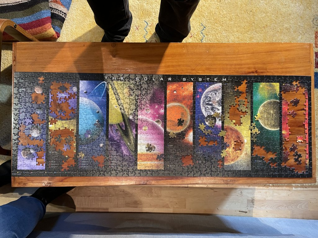 Top-down photo of an almost-complete 1000 piece jigsaw of the solar system.